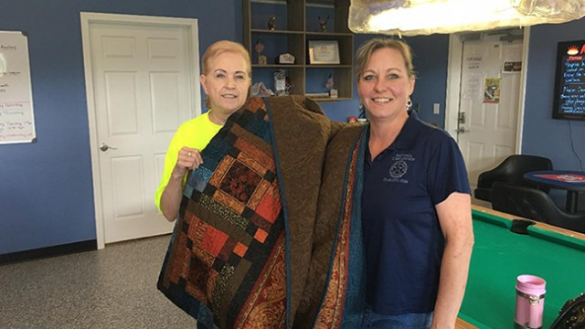 REGINA BIDWELL, PRESIDENT, American Legion Auxiliary Unit #217, Warsaw, presents the beautiful quilt that was made and donated by Lori Vannatta and At the Lake Quilt Shop located on MM Hwy in Warsaw, to our winner, Ann Peters.