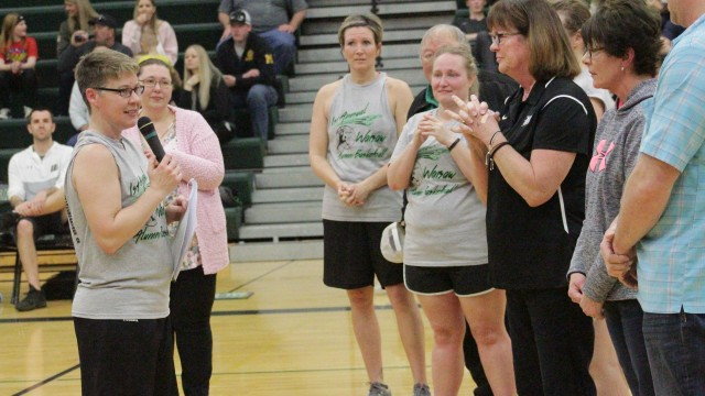 WARSAW 1989 GRADUATE SANDY PARKER spoke emotionally about the late girls basketball coach Don Dixon at the Alumni Game on Saturday night at WHS. Don's wife, Maxine (in black), and all of the girls Dixon coached were at half court during the half time ceremony.