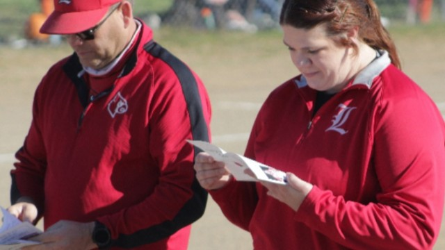 LINCOLN COACHES CHRIS SANDERS AND KELLY DEHAAN look over a program before a big game. DeHaan is the new Athletic Director at Lincoln added to her other duties. She had a great high school and college career in softball. Below is her amazing story.