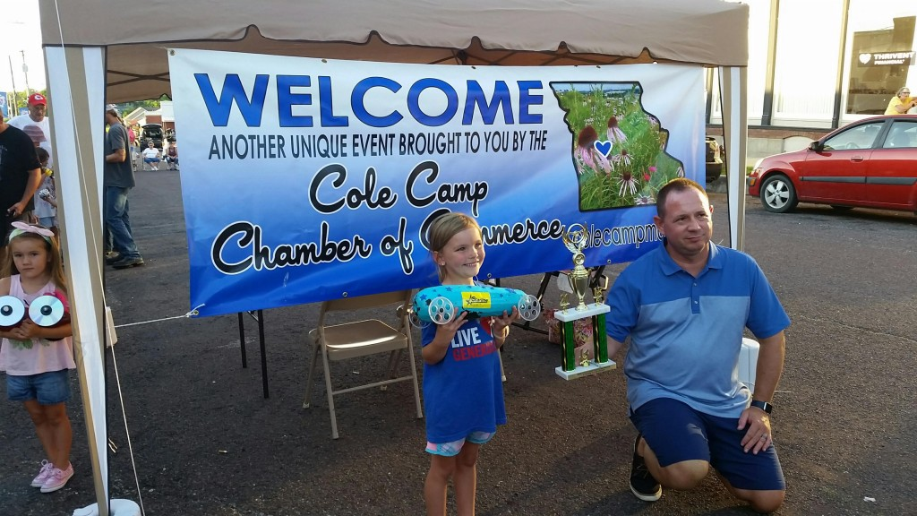 SHOWING OFF TALENT AND CREATIVITY, McKinley Brandis took home the top prize at the Annual Cole Camp Zucchini Race on Saturday. Presenting her award was event Chairman Tim Kreisel