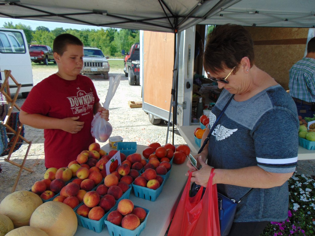 CULTIVATING COMMUNITY at the Farmers Market in Warsaw, Debbie Cox purchased peaches at Trent Downing's stand.