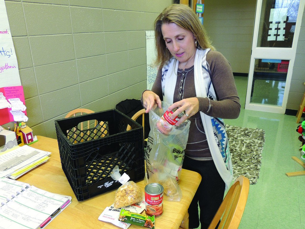 PREPARING A FOOD FILLED 'BUDDY PACK', Warsaw R-IX Counselor Teresa Flores says the program helps feed hungry children so they can learn and gives them something to look forward to on the weekend.
