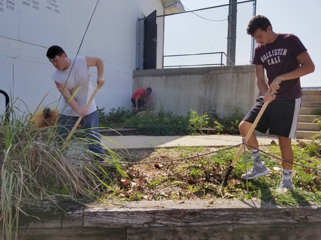 FRIDAY WAS COMMUNITY GIVE BACK DAY for the Warsaw football team. Players offered their time and services at various places around town for clean up and repair projects. Juniors Grady Miller and Gavin Roth worked at the WHS football field in the flower gardens.