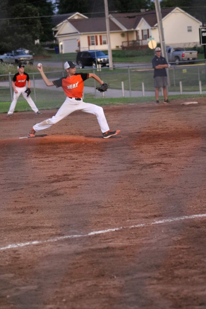 T.C. HAMBRICK DELIVERS another strike in a win earlier this season for his Heat squad.  Hambrick is a long-legged flamethrower who has helped his team not only on the mound, but at the plate and on the basepaths with his speed, as well.