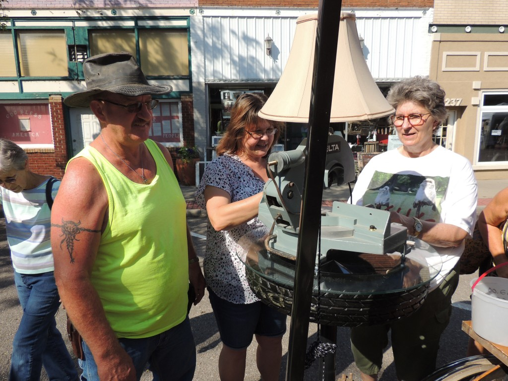 A BIG HIT ON WARSAW'S DOWNTOWN STREETS, Saturday's Junk Market drew a large crowd including Bill and Laurie Kedigh who perused items displayed by Martha Fann.