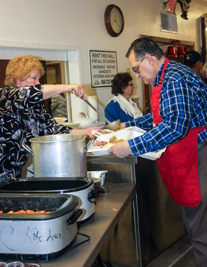 THE SPIRIT OF THE SEASON filled the Warsaw Knights of Columbus Hall on Christmas Day as the organization hosted a complimentary dinner that was open to all members of the community. Helping with  the event were Mary Kemna and Jack Hahn.