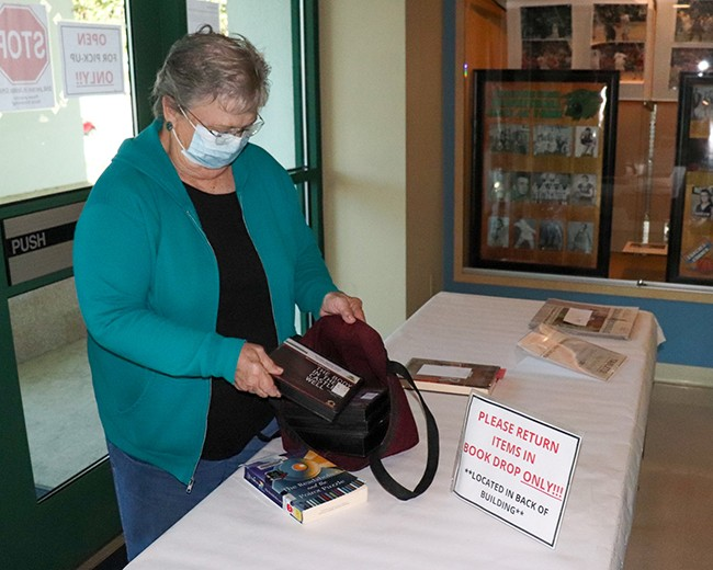 SERVING THE PUBLIC during the pandemic has brought challenges to the Boonslick Regional Library in Warsaw. Patrons including Clures Rhodes pick up books left for them in the entryway.