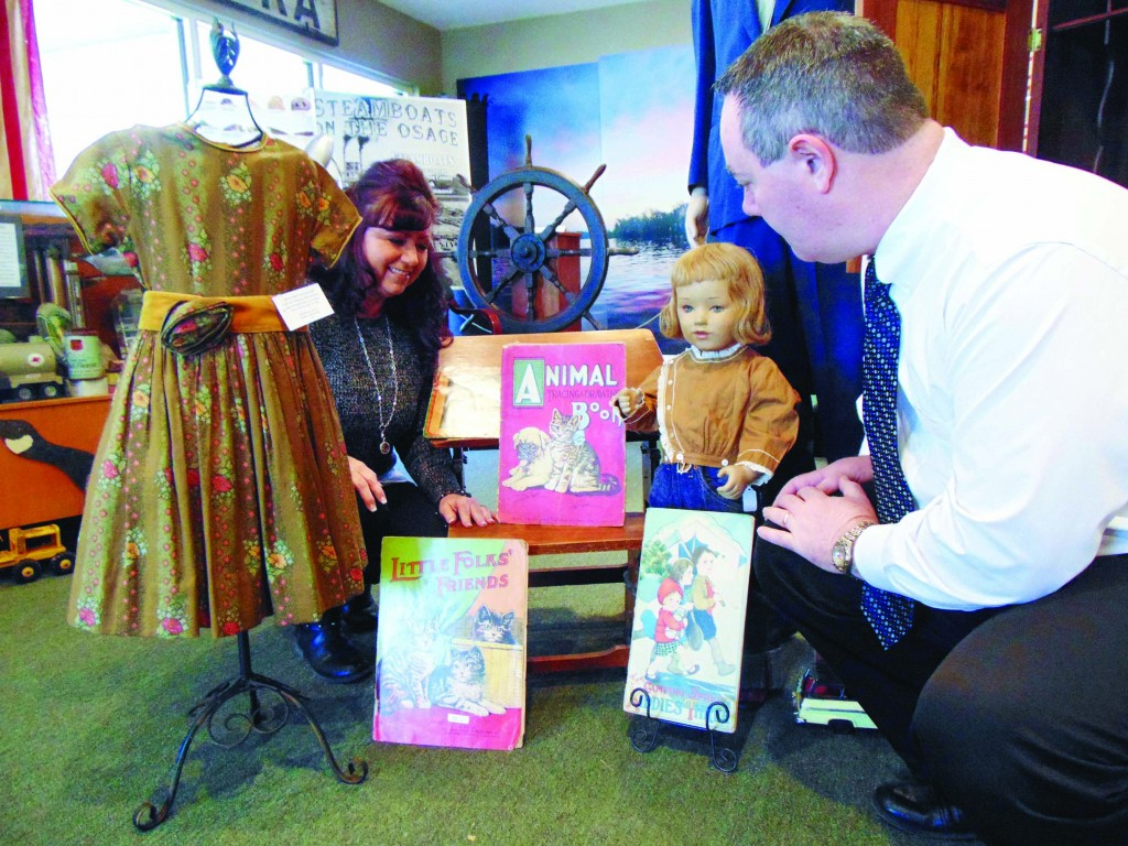 TOURING the new exhibits at the Benton County Museum, Kathy Arnett and Corbin Cain examined childhood items which were donated by Mary Jane Drake Cone.  The artifacts are part of a new series highlighting family history.