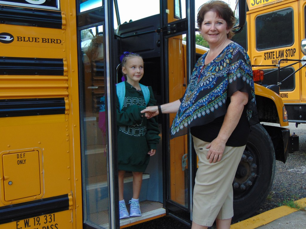 A NEW SCHOOL YEAR got underway on Tuesday at Warsaw's R-IX District. Librarian and Bus Guru Kim Flippin gave a warm Wildcat greeting to Jazzmine Clark, who begins first grade this year.