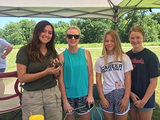 TRUMAN STATE PARK was a flurry of activity during Saturday's inaugural Outdoor  Safety Day.  State Park Naturalist Bailey Sharp took part in the program, displaying a native Missouri snake to Jennifer Neidholdt, Addison Fox and Avery Neidholdt.