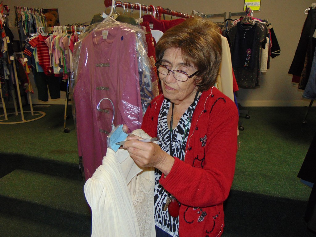 PREPARING FOR A FLEA MARKET FUNDRAISER, Place At The Lake Thrift Store Volunteer Margaret Duft tagged items on Tuesday. The organization is staging a major sale this Friday and Saturday in Lincoln to raise funds for domestic abuse victims.