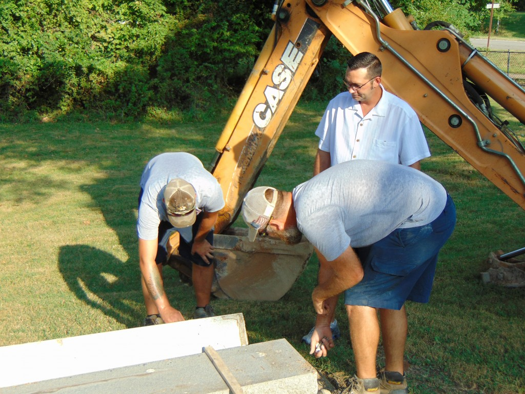 RESTORATION IS UNDERWAY at the Old Warsaw Cemetery to repair recent vandalism. Kyle Slagle and Brandon Zaring from Wommack Monument Company and Alderman Eric Masoner worked to raise Jonas Alexander's tombstone.