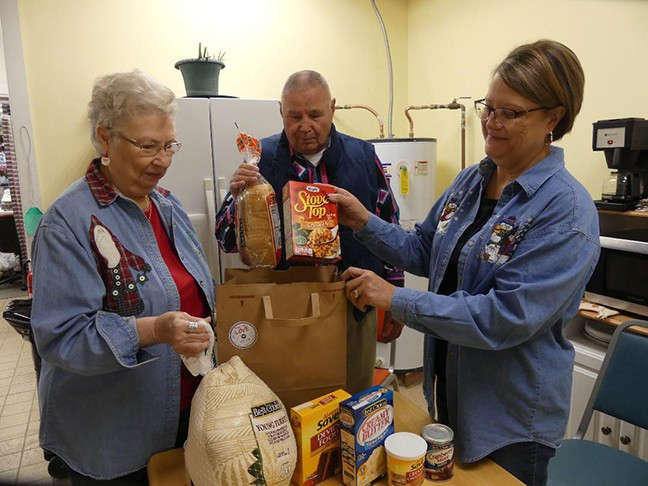 THE WARM HOUSE was a flurry of activity on Friday as volunteers including Linda Sinnett, Larry Konopasek and Sue Stevens packed items to help area families in need with Christmas dinner.