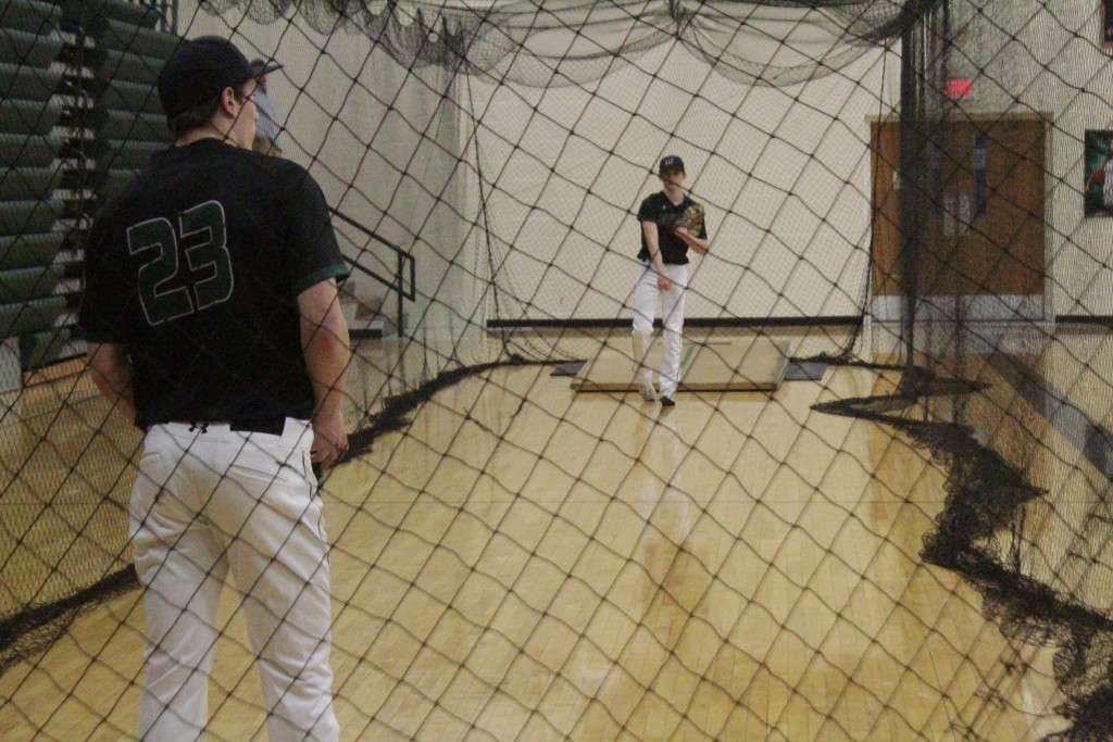 WARSAW SENIOR RILEY BAGLEY PLAYS CATCH with Senior Matt Luebbert (23) inside the netted batting cage inside the gym at WHS. The other sports, track, golf and archery are all also practicing indoors due to the incumbent weather conditions.