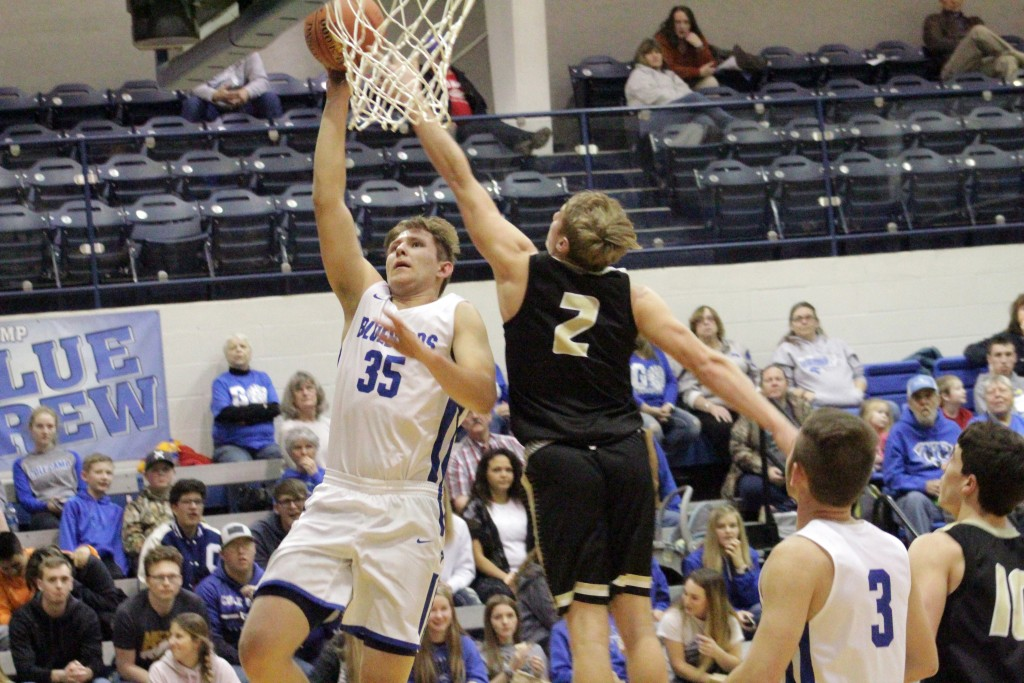 COLE CAMP'S RUVIM GARBUZOV lays the ball in over the outstretched arm of Versailles Brayden Morrsion in Friday's showdown at Cole Camp. The Bluebirds avenged an earlier two point loss with a 82-80 victory over the Tigers. Coby Williams had 43 for Versailles.