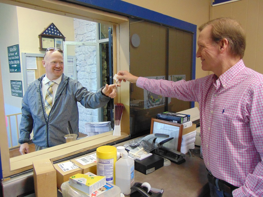 GETTING DOWN TO BUSINESS, Warsaw Chamber Director Mac Vorce accepted the keys to the organizations new office from Warsaw Mayor Eddie Simons at the Community Building.