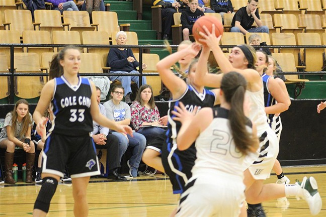 COLE CAMP'S ASHLEY SCHEAR watches as Aubrie McRoberts puts up a jumper in the lane for Warsaw. Cole Camp won 59-50 in season opener for both teams.
