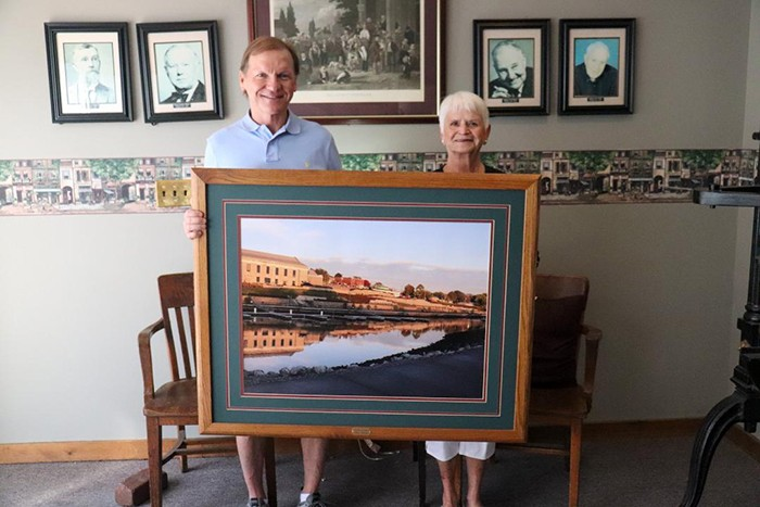 DONATING HER TIME AND TALENT, Betty Hollcroft presented Mayor Eddie Simons with a magnificent, framed picture of Drake Harbor. It will be on display at the city office.