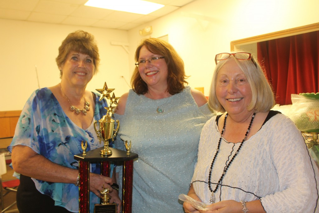 TAKING HOME THE TOP PRIZE for their table decoration at the Benton County Food Pantry's gala dinner were the Friends Of The Benton County Sheriff's Office. Accepting the trophy on behalf of the organization were Janet Manson, Carrie Rieman and Lonnie Taylor