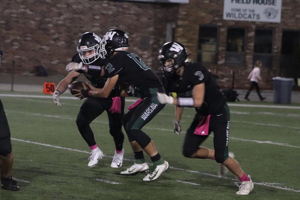 WARSAW'S AIDEN COMER TAKES THE HANDOFF from quarterback Matt Couzens on one of his 32 carries on the night in the Cats game versus Father Tolton Catholic last Friday.  Comer finished with 289 yards rushing and was assisted out of the backfield often by running mate, Chase Steiner.  Photo courtesy of Kya Schepker, The Wildcat.