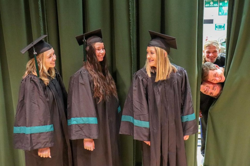 MAKING A PRACTICE RUN, Jessie Glenn, Kamryn Yach and Suzanne Cortright strolled across the WHS stage before the official ceremony set for this Friday evening. Looking on were fellow graduating seniors Evan Kowal, Maleek Porter and Jacob Luebbert.