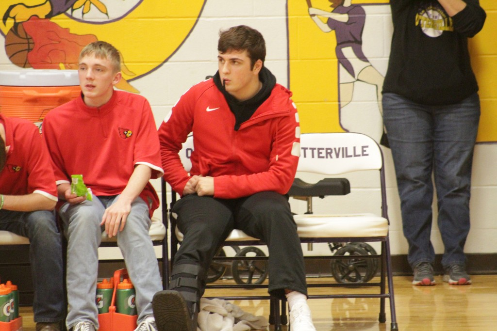LINCOLN JUNIOR NATE HESSE sits and watches at his team plays against Smithton in the Otterville Tournament last Thursday. Hesse broke his foot in practice last week and could be out for three weeks or longer.