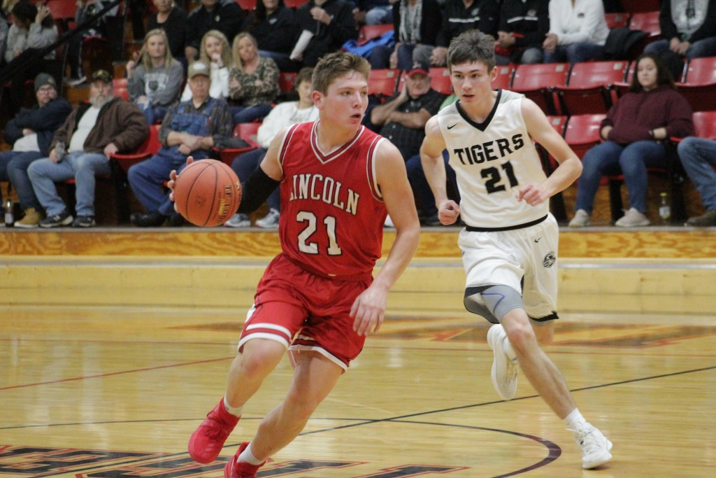 IT WAS THE BATTLE OF THE #21'S as Lincoln's Jackson Beaman drives around Skyline's Ethan Edwards during Thursday night's contest at Urbana Skyline won 67-46.