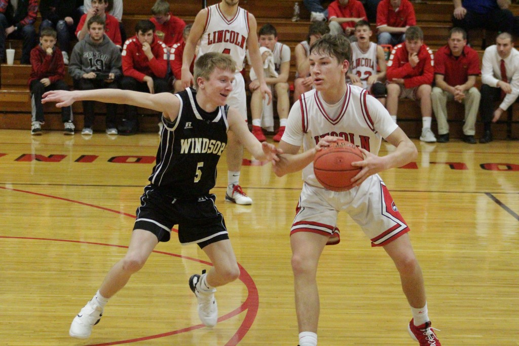 LINCOLN'S BO KROENKE is guarded by Windsor's Jacob Berube during last Tuesday night's game against an upstart Windsor team. Lincoln won 48-43. Kroenke went on a tear in the  first half with 18 points and ended with a game high 24.