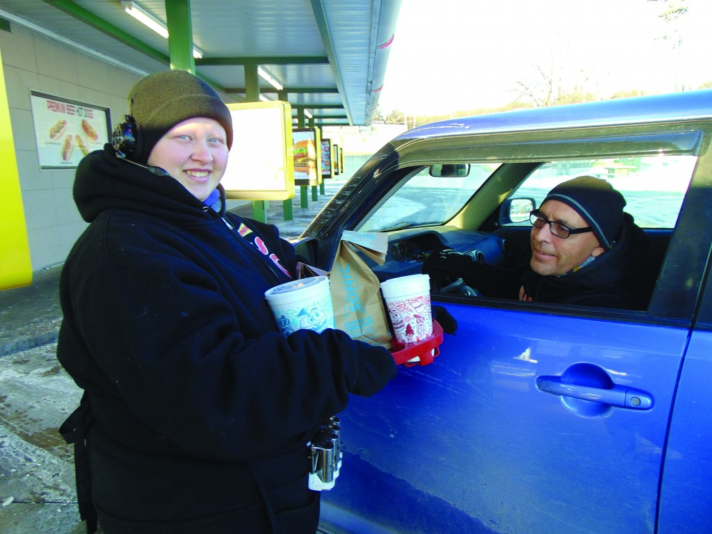 "COLD TEMPERATURES ARE JUST A PART OF THE JOB for many workers, including Warsaw Sonic car hop Casey Keith who delivered a breakfast order to Jamie Lux. She told the Enterprise, ""I bundle up as much as I can. I wear three coats, a hat, gloves and get on with it."" The wind chill was 16 degrees below zero early Tuesday,"