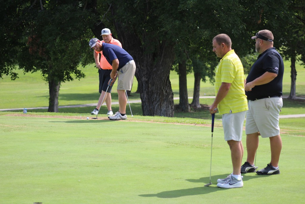 JAYSON FOWLER PUTTS as Brandon Garber looks over his shoulder on the ninth hole at the Shawnee Bend Golf Course on Saturday at the 34th Annual 3-person Scramble for the Warsaw Cup. Rod Carmack and Bob Wolf look on. Rain and lightning on Sunday shorted the tournament to 27 holes.