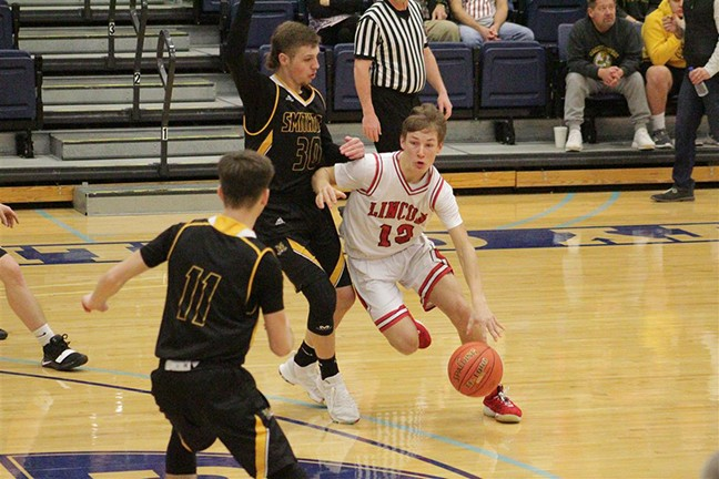 BO KROENKE DRIVES around two of Smithton's defenders in Lincoln's first round win in the Kaysinger tournament on Saturday afternoon.