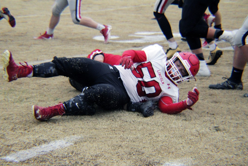 IN A KNOCK DOWN, DRAG OUT CONTEST, Lincoln Senior Clayton Kreissler lays on the leg of a fallen Lockwood player. This typifies the hard hitting battle with Lockwood on Saturday in the state quarterfinals. Kriessler was a true warrior on the offensive line and at linebacker all season. Lincoln lost 40-33 and ended up 11-1