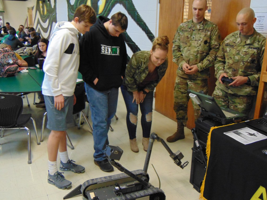 IROBOT 510 PACKLOT took center stage at Warsaw High School on Tuesday as Sergeants First Class Brandon McConaha and Thomas Mortimore demonstrated its abilities to faculty and students including Brady Slavens, Virgil Goucher and Taylor Bunch. The robot is designed to perform a multitude of dangerous tasks without risking human life.