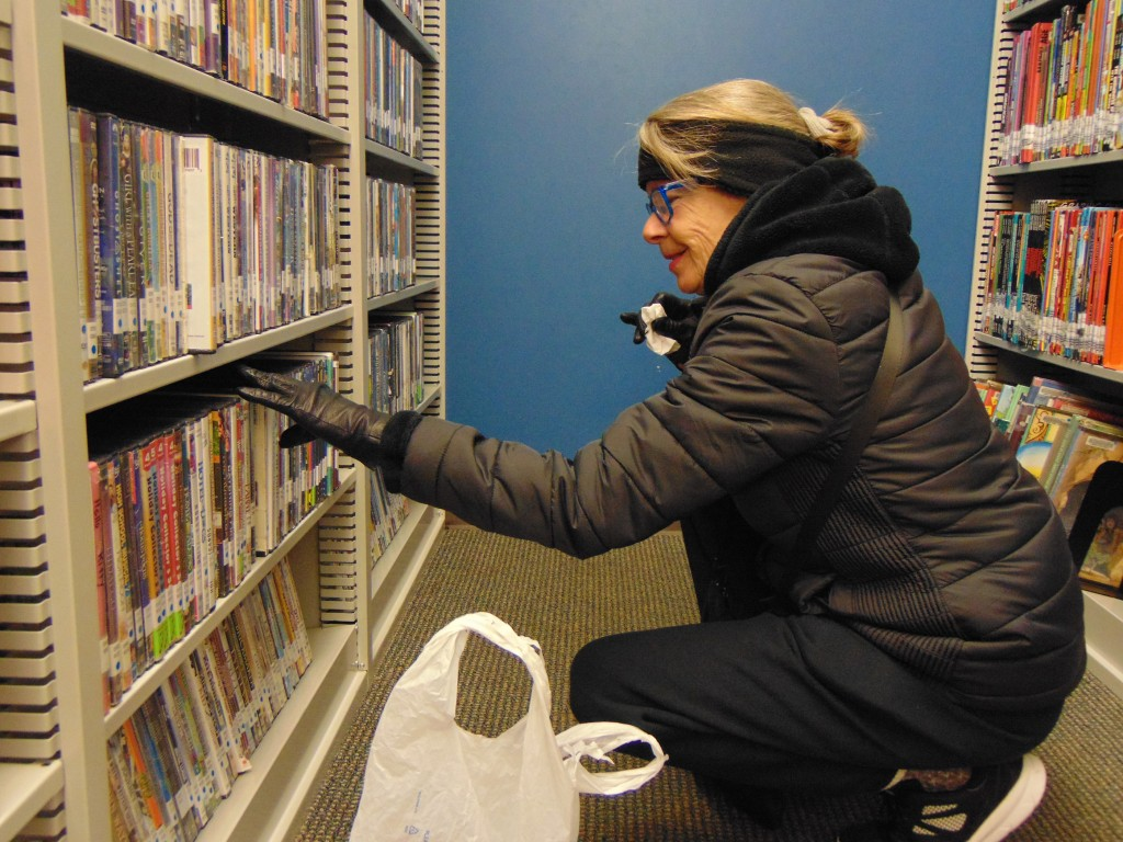 KEEPING CABIN FEVER AT BAY, the Boonslick Regional Library in Warsaw is offering an array of programs this winter. Robyn Carr perused available movies on Tuesday to take home before the expected snow storm.