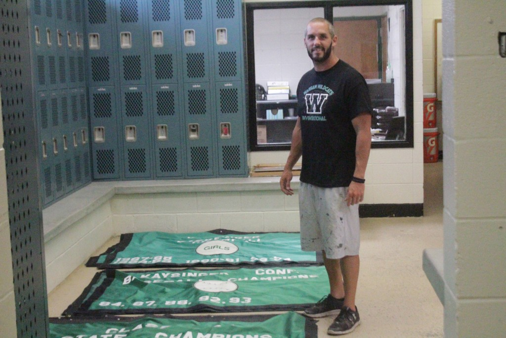OUT WITH THE OLD AND IN WITH THE NEW. Head Football Coach and Athletic Director Ryan Boyer stands in the boys locker room along side the old WHS banners. Joining the new Ozark Mountain Conference led to the decision to replace the old banners.