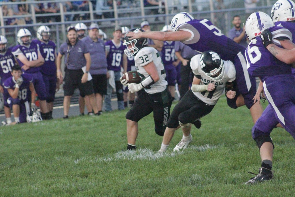 WARSAW'S ZACH CHAPMAN MAKES THE BLOCK of his career against Midway as Aiden Comer runs around the right side. Warsaw would  win their season opener on the road 14-6. They will play Knob Noster this Friday.