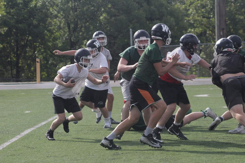 FRESHMAN QUARTERBACK NICK BAGLEY runs behind his line during football camp at WHS. Some 50 boys showed up to camp. Warsaw looks to improve on their 2-8 record of a year ago.
