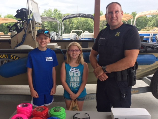 INFORMATIVE FUN was in the air during the First Annual Jr. Angler's Camp hosted by Angler's Port Marine in Warsaw. MO State Highway Patrol Trooper Baughman gave a presentation on Water Safety to attendees including Evan Schoessel and Isabella Grace.