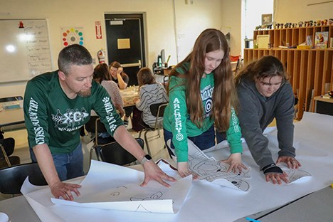 IN THE MIDST OF MURAL CREATION, long time John Boise Middle School art teacher, Christian Condray, assisted Alyson Alcantara and Erin Goodpaster in the layout of the artwork. The Summer Reading program at the Boonslick Regional Library in Warsaw begins on June 1, 2019.