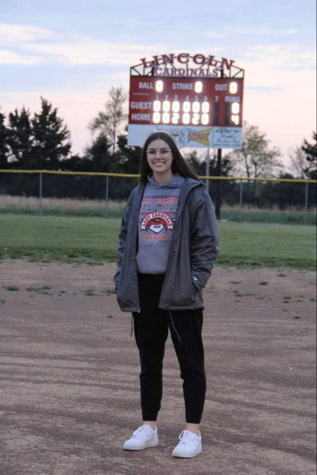 A SAD GOODBYE Lincoln senior Chloe Reese stands on an empty softball field. In the background is the scoreboard that reads 2020 in honor of the seniors. Reese was All -Conference basketball,  All- State volleyball and a defensive gem on the 2019 state champion softball team.