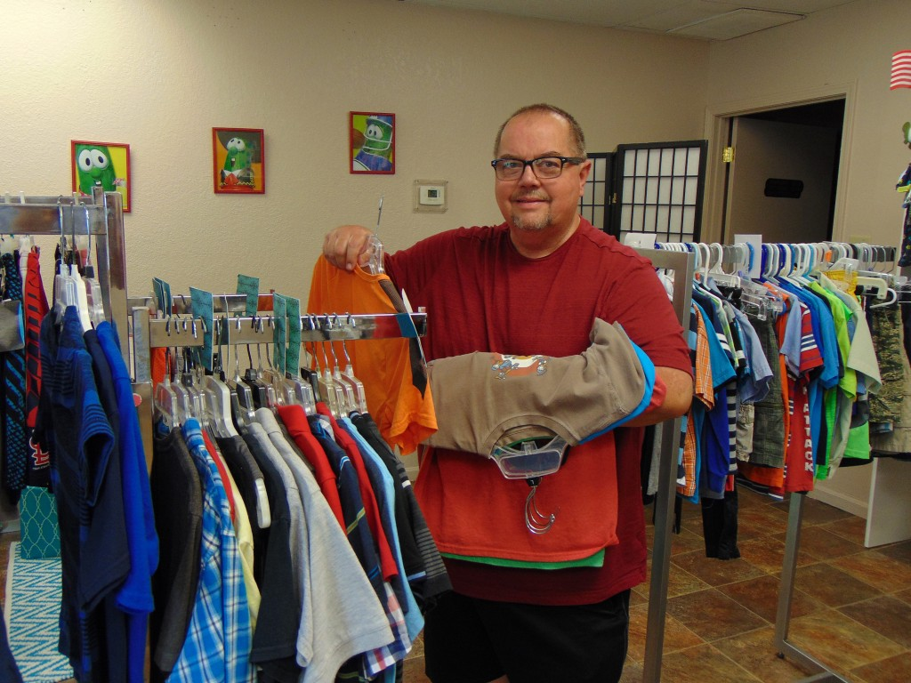 GIVING A BOOST to kids, the Family Resource Center in Warsaw has a host of helpful programs, including free clothing for children up to age 18. Charlie Ruble stocked apparel racks on Tuesday in anticipation of increased fall demand as schools resume.
