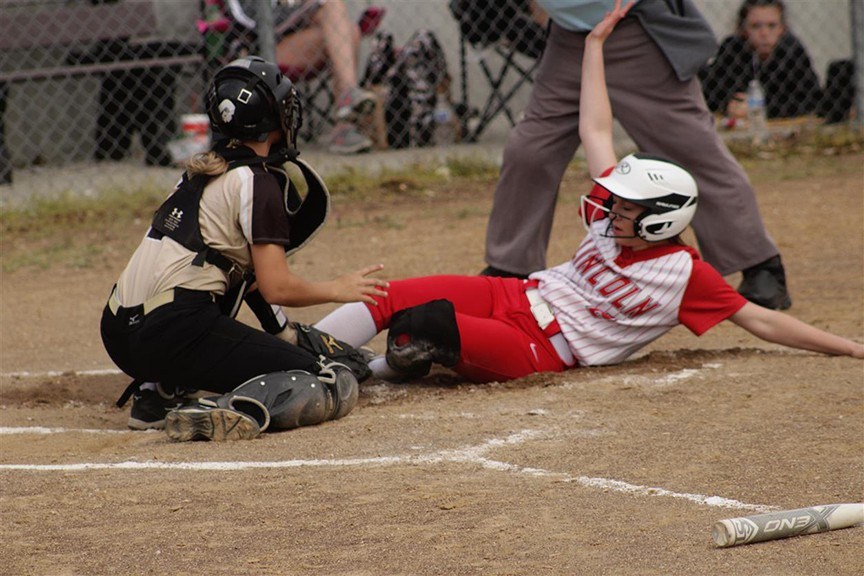 JORDAN YOUNG SCORES on a close play at the plate in the third inning in Monday's game on Senior night. The Lady Cardinals beat Adrian 4-1.