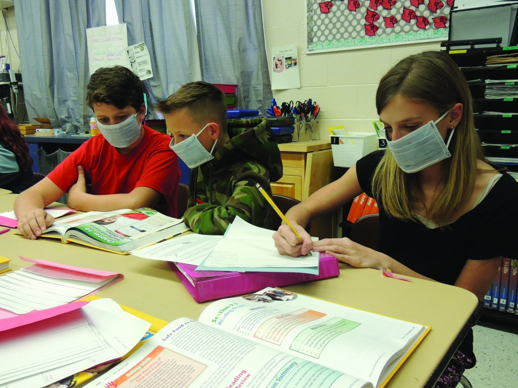 NOT TAKING ANY CHANCES, Lincoln Junior High students Audrey Sassmann, Kaleb Mundy and Mack Hesse wore masks to help prevent contracting the norovirus that caused the school to be closed for two days last week.