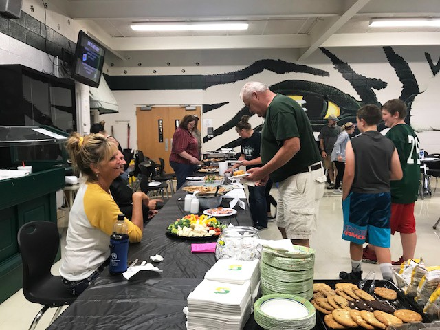 A FOOTBALL FEEDING FRENZY, Lori Dunkin and Chuck Allcorn participated in Friday evening's Quarterback Club tailgate dinner. The event was sponsored by the Warsaw Area Chamber of Commerce.