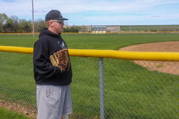 """WILDCATS BASEBALL PLAYER Logan Strunk looks out onto the baseball field, wondering """"what might have been"""" had his team gotten to take the field this season.  MSHSAA officially cancelled all spring sports as an effect of Governor Parson's call to cancel all schools for the remainder of the academic school year last week."""