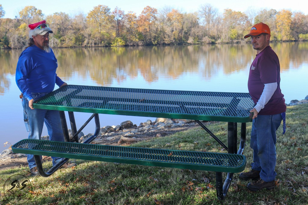 HITTING DRAKE HARBOR again and again, vandals continue to dump picnic tables into the Osage River. City of Warsaw Employees Les Day and Philip Pierce are charged with getting them out of the water.