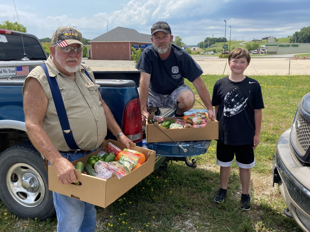 CARS POURED into the parking lot at Warsaw's NAPA Building as Lincoln VFW volunteers, including Ray, Steve and Colton Reedy, helped distribute boxes of produce.
