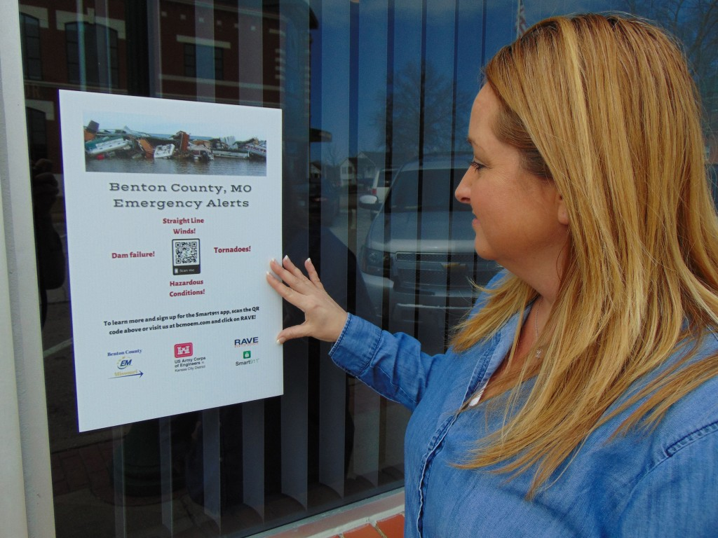 STRESSING THE IMPORTANCE of prior notification of emergencies, signs have been placed around Benton County that encourage people to sign up for RAVE. Angela Parrott reviewed the information posted at a Warsaw Main Street business.