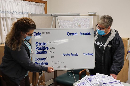 PUBLIC HEALTH HEROES include Barbara Schroder and Linda Viebrock. The duo tracks cases and keeps them updated on a whiteboard at the Benton County Health Department.