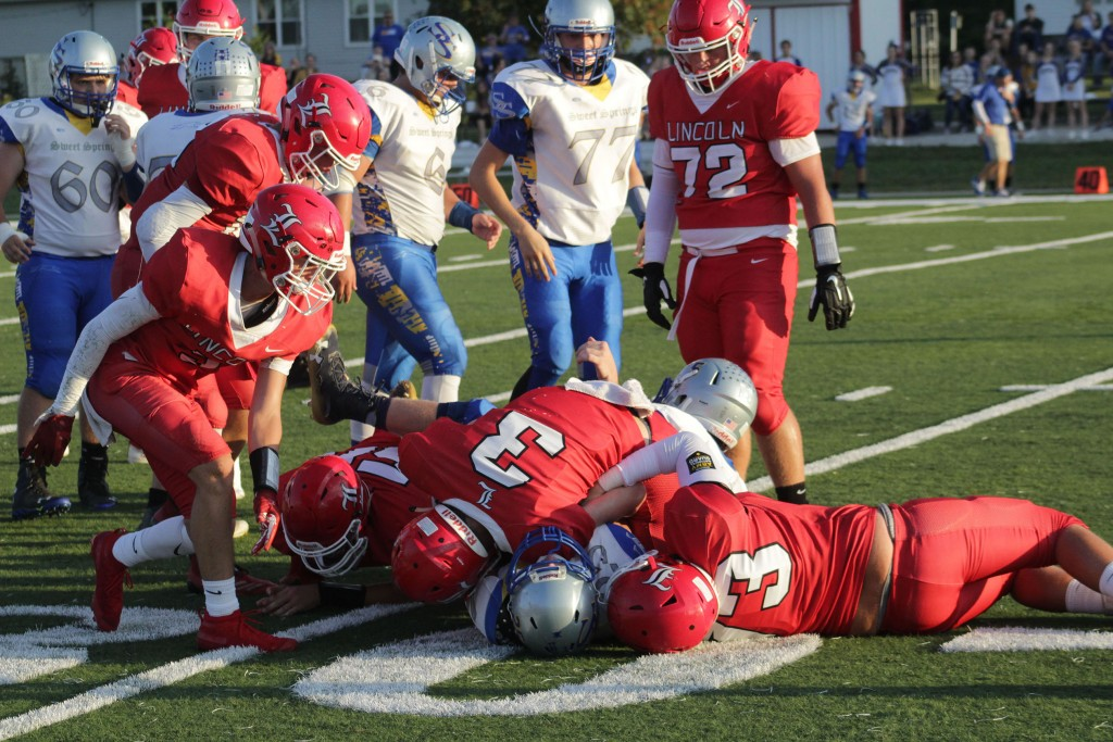 SOMEWHERE UNDER THE PILE IS THE SWEET SPRINGS QB as Lincoln's Parker Engles (#3), Hayden Beaman (#73) and Tanner Bays (#55) make the tackle. Lincoln won 49-12 at home on Friday to remain unbeaten at 5-0 and #1 in Class 1.